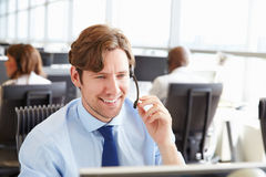 Man working in a call centre,holding headset, close-up Royalty Free Stock Photos