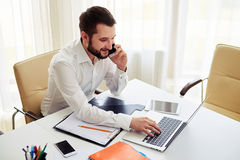 Man working and calling someone on the smartphone in the modern. Man working on the laptop and calling someone on the phone in the modern white office, view from stock photography