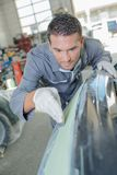 Man working car bumper Stock Image
