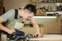 Man working with carving equipment at workshop. Chinseling groove stock photos