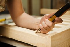Man working with carving equipment in workshop holding chisel. Man working with carving equipment in workshop. Manual making of chinseling groove in wooden bar stock photos