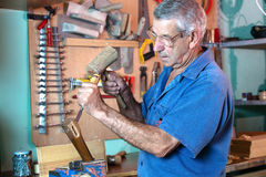 Man working carving wood with a chisel and hammer. Carpenter in the workshop handling a chisel and a hammer on a piece of wood royalty free stock photos