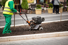 Man working in the city streets with Garden Tiller. Close-up male plow. Cultivator machine. Royalty Free Stock Photography