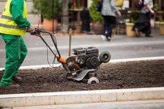 Man working in the city streets with Garden Tiller. Close-up male plow. Cultivator machine. Royalty Free Stock Photos