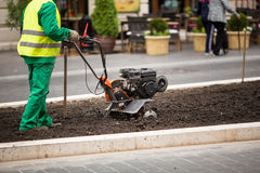 Man working in the city streets with Garden Tiller. Close-up male plow. Cultivator machine. Royalty Free Stock Photo