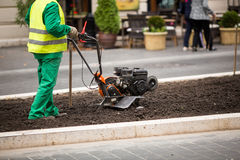 Man working in the city streets with Garden Tiller. Close-up male plow. Cultivator machine. Stock Photos