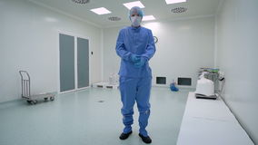 A man working in a clean room, pharmaceutical enterprise. Specialist in a protective suit, gloves, glasses and a mask. stock video footage