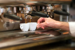 Man working in a coffee house preparing espresso. Close up view of the hand of a man working in a coffee house preparing espresso coffee Royalty Free Stock Photo