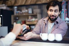 Man working in a coffee shop taking cashless payment. Middle-aged man working in a coffee shop taking cashless payment by credit card blurred smiling looking at Royalty Free Stock Photos