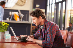 Man working on computer at coffee shop stock images