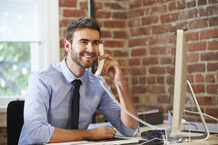 Man Working At Computer In Contemporary Office Stock Photos