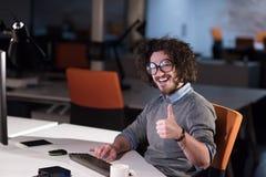 Man working on computer in dark startup office Stock Photo