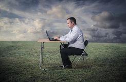 Man working at the computer. A man working at the computer in a field Royalty Free Stock Photo