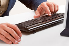Man Working at a Computer Keyboard Royalty Free Stock Photos