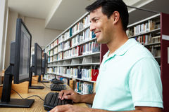 Man working on computer in library Stock Image