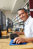 Man working on computer in library Stock Photography