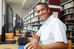 Man working on computer in library Stock Images