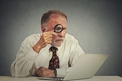 Man working on computer looking through magnifying glass at screen Stock Photo