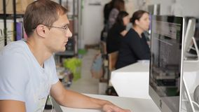 Man is working at a computer in a noisy and crowded office. Male employee is focused on working with monitor in environment of employees, who are their own stock video