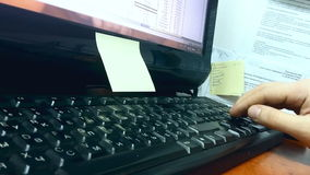A man working at the computer. A man is siting at the workplace and typing with one hand on keyboard in front of monitor stock video