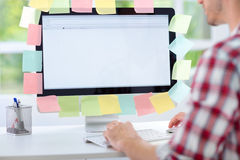 Man working on computer with sticky notes. Back view Royalty Free Stock Photo