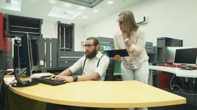 Man working on computer and talking to his colleague with tablet. Adult bearded worker at computer then typing on tablet and talking to female co-worker stock footage
