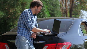 Man working on the computer in the trunk of car stock video