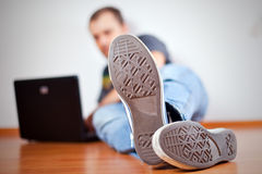 Man working with computer on wooden floor. The man working with computer on wooden floor.  view on outsole Royalty Free Stock Photos