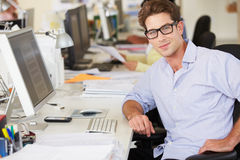 Man Working At Desk In Busy Creative Office Royalty Free Stock Images