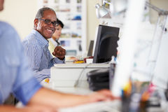 Man Working At Desk In Busy Creative Office Royalty Free Stock Photos