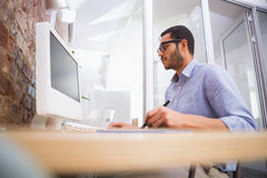 Man working at desk with computer and digitizer Royalty Free Stock Images