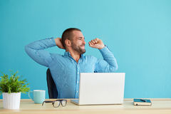 Man working at desk in office. Stretching his back at desk Royalty Free Stock Photo