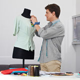 Man working on dress form Stock Images
