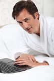 Man working in dressing gown. Stock Photos