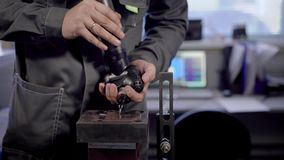 Man working with drill. Crop view of man in gray uniform with ring on finger working with drill in workshop on blurred background of table with computer stock footage