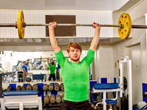 Man in working with  dumbbells his body at gym Stock Photo