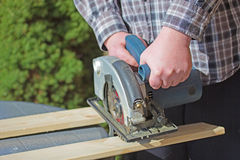 Man is working with electric circular saw Stock Image