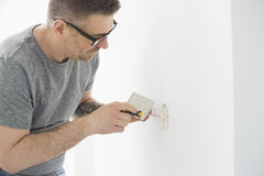 Man working on electrical outlet Royalty Free Stock Photography