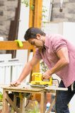 Man working with an electrical sander Stock Photos