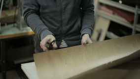The man working at the factory. Cuts cardboard frame for making handbags. stock video footage