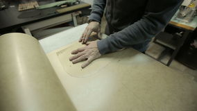 The man working at the factory. Cuts cardboard frame for making handbags stock footage
