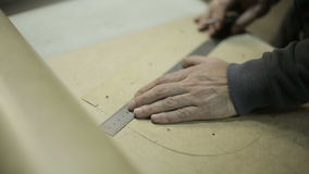 The man working at the factory. Cuts cardboard frame for making handbags stock video