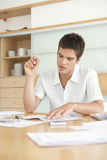 Man Working on Finances. Portrait of young man working on his home finances in the kitchen Royalty Free Stock Image