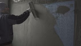 A man splashes a wall with a spatula. A man in a working form with a spatula plasters a wall with a gray mortar over a superimposed grid