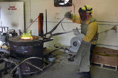 Man Working in the Foundry Hot Furnace. Man working in the foundry at a furnace putting ore into a crucible to melt, wearing protective gear. Dangerous work Stock Photos