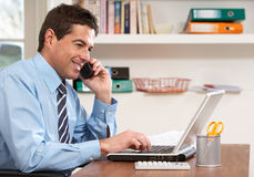 Man Working From Home Using Laptop On Phone Stock Photos