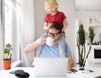 Free Man Working From Home With Laptop During Quarantine. Home Office And Parenthood At Same Time. Exhausted Parent With Hyperactive Royalty Free Stock Images - 179928349