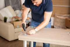 Man is working with furniture assembly using electric screwdriver in new house. Man using tools royalty free stock photography