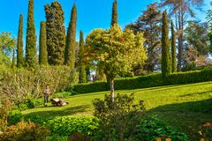 Man Working In Garden Cutting Grass. Lloret de Mar, Spain - April 11, 2017: Man Working In Garden Cutting Grass With Lawn Mower in the Santa Clotilde Gardens in Royalty Free Stock Photos