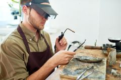 Man Working with Gas Torch. Side view portrait of young man holding small gas torch and welding tools while working with metal against shabby wooden workstation Stock Photos
